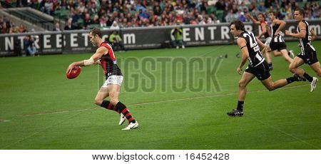 MELBOURNE - APRIL 25: Collingwood's Steele Sidebottom (R) chases Mark McVeigh of Essendon in Collingwood's massive win over Essendon - April 25, 2010 in Melbourne, Australia.