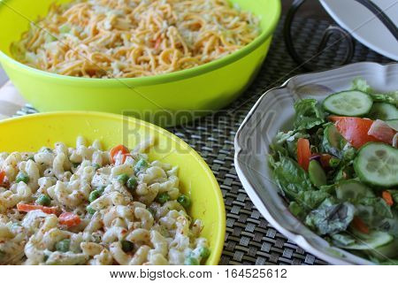 Macaroni with green salad and noodle close-up