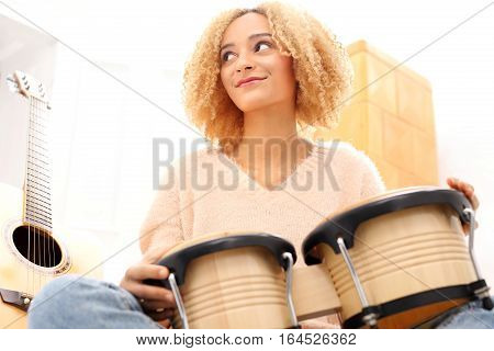 Create your own music. Tapping the rhythm on the drums. Bongos, percussion. Girl playing bongo drums, small drums.