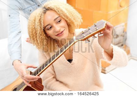 Guitar lessons. Acoustic guitar. Relax while playing the guitar. Girl playing the guitar. The girl guitar tunes. Play on the instruments.
