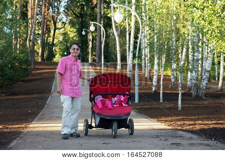 young man with double pram and two kids in it