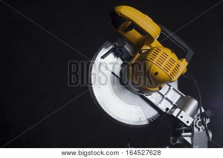 miter saw. Cutting disk on black background