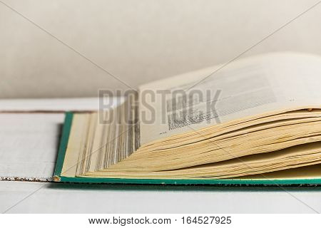 Close up image of open old book on white wooden background. Copy space