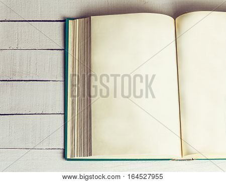 Open book on wooden background. Back to school. Copy space. Top view. Toned retro image