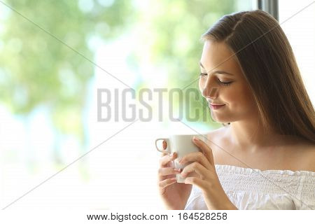 Romantic attractive girl thinking and looking down at coffee cup at home near a window with a natural green background outdoors