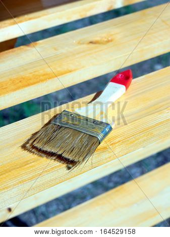 Brush lying on a painted wooden shelving surface. Vertical photo closeup
