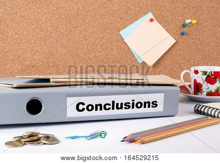 Conclusions. Folder, Coffee Mug, colored pencils on wooden office desk.