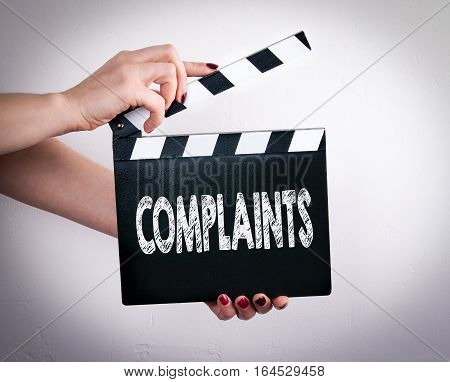 Complaints. Female hands holding movie clapper. Gray background.
