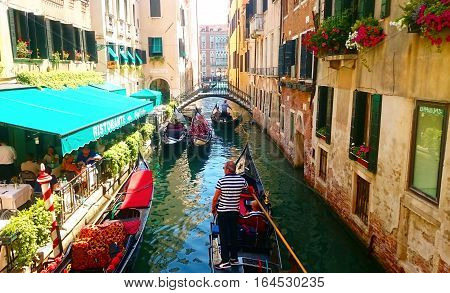 Gondolas on Canal in Venice, Italy. With a beatifull old buildings and flowers arround.