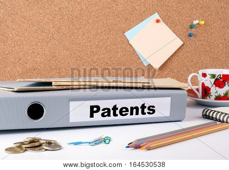 Patents. Folder on office desk. Money, Coffee Mug and colored pencils.