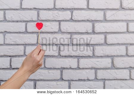 Woman's hand holding red heart shape on stick. White brick wall baskground. Valentine concept
