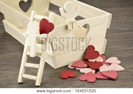 Wooden figure with heart rises ladder to visit a girl