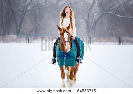 Young girl enjoying horseback riding in winter park