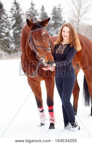 Young rider girl standing with bay horse in winter park