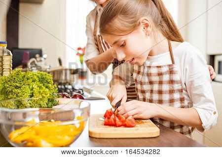 Young teenage girl cooking together with her family in the kitchen. Cute girl chopping tomatoes for salad