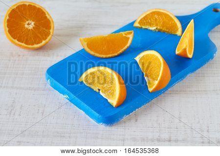 Orange slices on vintage blue wooden kitchen board