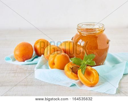 Jam from apricots in a glass jar on a wooden surface