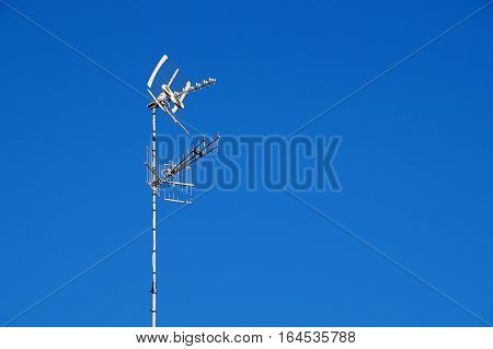 television antenna set against a blue sky