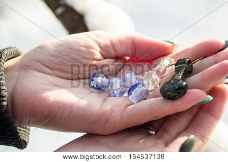Woman hand with blue glassbeads closeup in winter day
