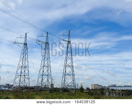 Electrical networks pylons in the field on a background of blue sky