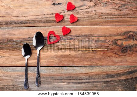Teaspoons near red hearts. Silver spoons on wooden background. Being always together.