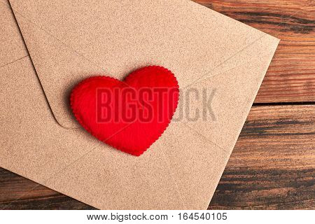 Red heart on envelope. Letter with heart on wood. Send love receive love.