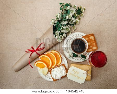 Romantic Birthday Healthy Breakfast.Cup of CoffeeCut Orange.Biscuit with Cottage Cheese.Glass of red Beverage.Wish Card with Flowers.Present in Golden Box