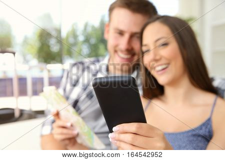 Couple of tourists searching location in a phone during vacations in an hotel or apartment with a window in the background