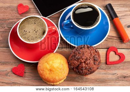 Hearts and muffins. Cups of coffee near tablet. Lovely morning with beloved.