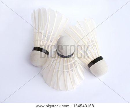 Three white feather badminton shuttlecocks top view closeup