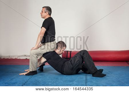 Kapap instructor demonstrates arm lock techniques with his student