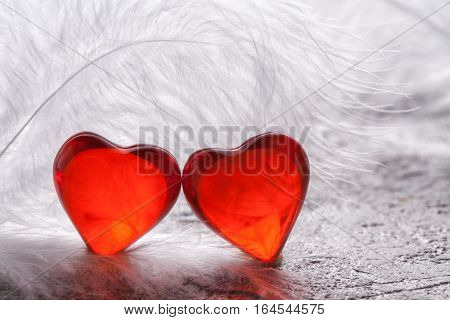 Red heart on a white feathers background