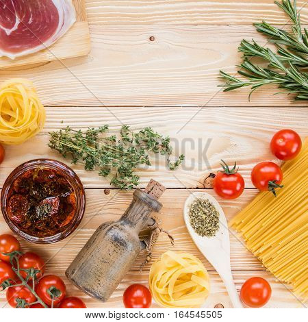cherry tomatoes dried tomatoes in glass jar on wooden table olive oil in clay jug top view italian food concept