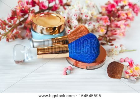 The Pink  Branche of Chestnut Tree,Bronze Powder with Mirror and Make Up Brush are on White Table