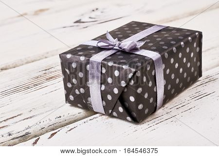 Present package and violet ribbon. Spotty gift box on wood. Gift wrapping tutorial.