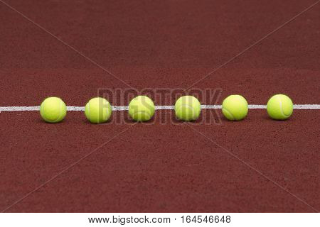 Six yellow tennis balls in-line on court with synthetic surface front view