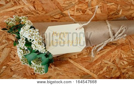 Birthday Card with Bouquet from White Flowers and Green Leaves,Craft Strong Brown Paper on the Texture Wooden Background.Celebrations Wishes,Happy Birthday