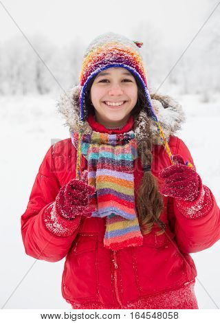 Adorable girl standing in colorful warm clothes on white snow landscape, outdoors winter vacation