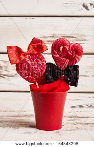 Red lollipops in flowerpot. Heart-shaped candies with bows. Sweet decoration for Valentine's Day.