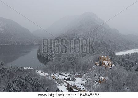 Mountain landscape in winter time with Hohenschwangau Castle, Alpsee Lake on the left and Schwanensee on the right. Alps on background. Bavaria. Germany.