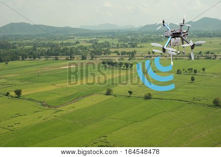 internet of things(industrial agriculture and smart farming concept)farmer use drone for keeping the data in the field by using the signal and the detector