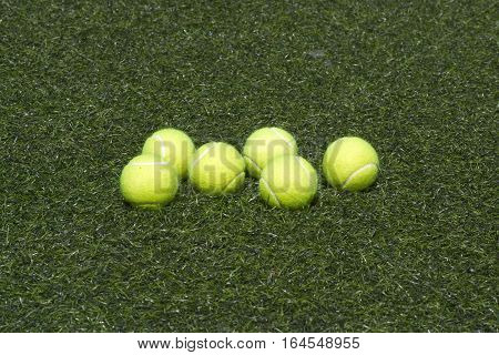 Six yellow tennis balls lays on green synthetic grass front view