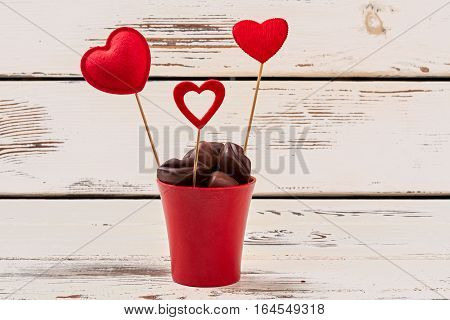 Flower pot with chocolates. Hearts on sticks on wood. In love with sweet tooth.