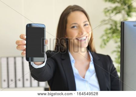 Happy businesswoman showing smart phone screen in her workplace