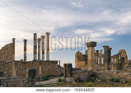 The exterior of the Basilica and the Capitoline Temple at Volubilis on a sunny day with few clouds and blue sky, Morocco.