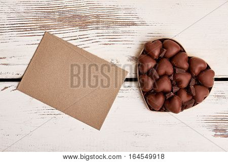 Blank paper and candies. Box of chocolates on wood. Send your best wishes.