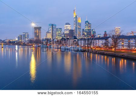 Picturesque view of business district with skyscrapers and Old Town witn mirror reflections in the river during morning blue hour, Frankfurt am Main, Germany