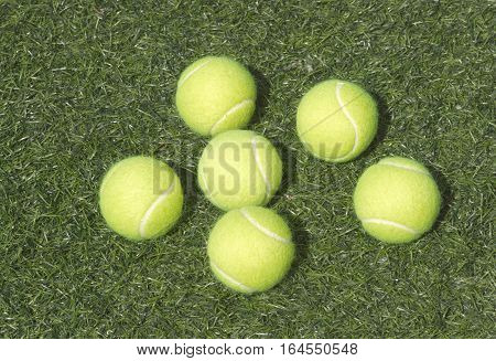 Six yellow tennis balls laya on green synthetic court grass top view