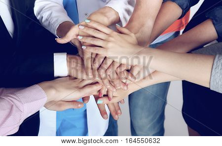 Portrait of people with various occupations putting their hands on top of each other.