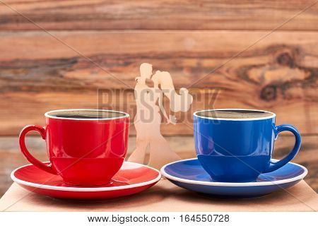 Mugs near wooden shape couple. Cups with coffee. Your portion of tasty refreshment.